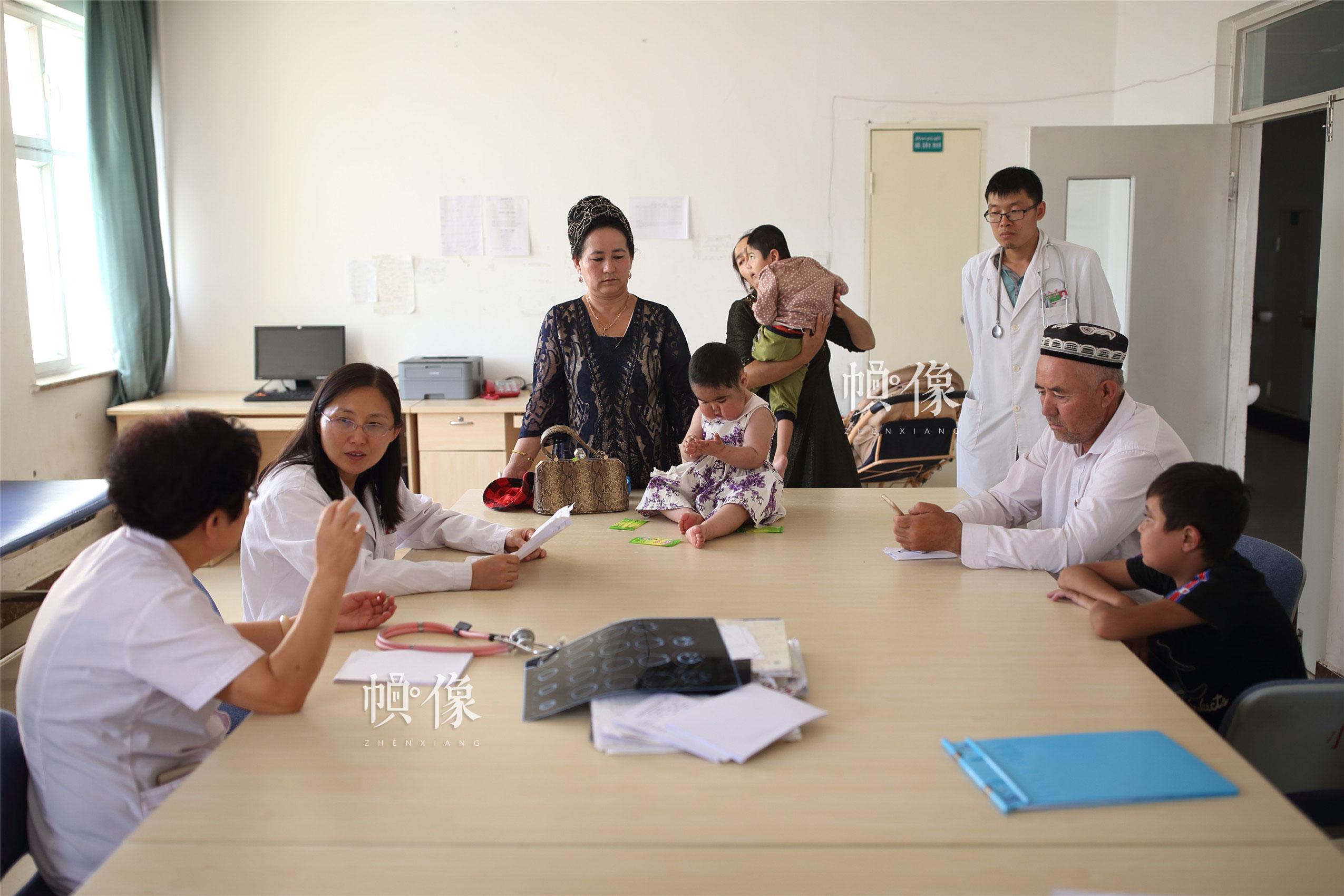 """北大医院主任医师、""""全国儿科医师专项培训项目"""" 培训课程设置负责人齐建光与新疆克州人民医院儿科主任韩建玲探讨儿童患者病情,多位儿童罕见病患者前来诊治。中国网记者 陈维松 摄"""