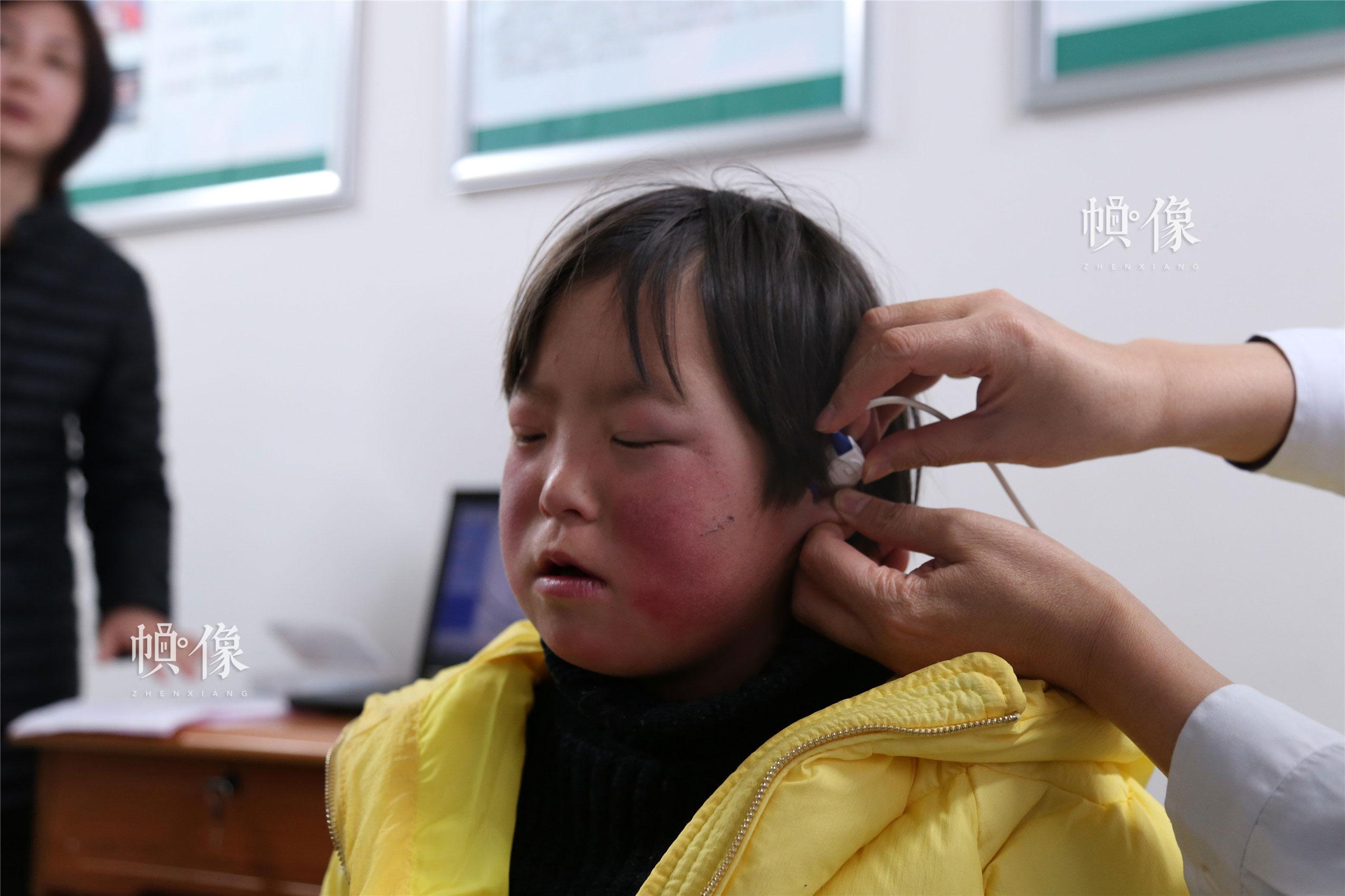 2018年1月22日,甘肃省陇南市西和县,医生通过医疗器具对听障儿童进行听力测试。中国网实习记者 朱珊杉 摄