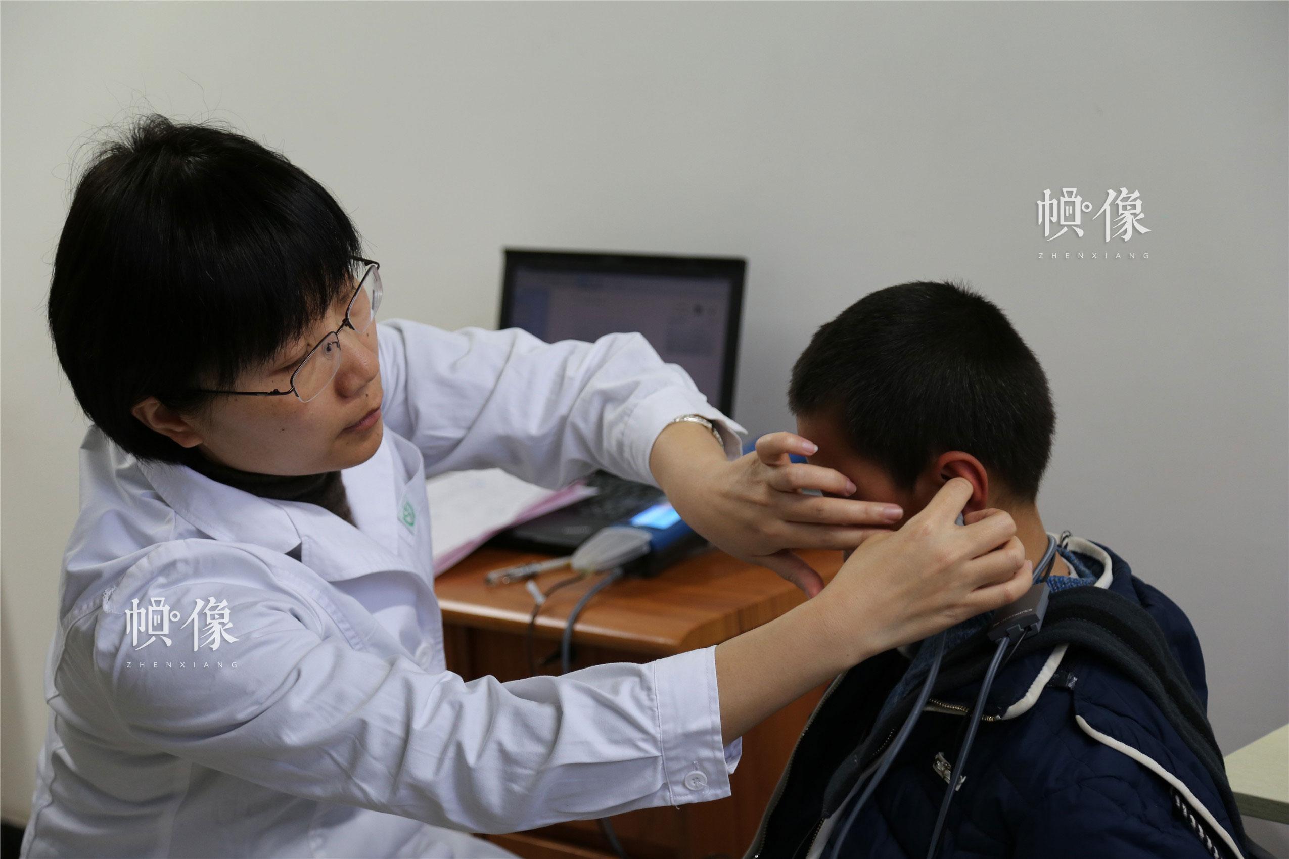 2018年1月21日,甘肃省陇南市西和县,精准扶贫医疗团队成员为听力障碍儿童进行筛查。中国网实习记者 李逸奇 摄