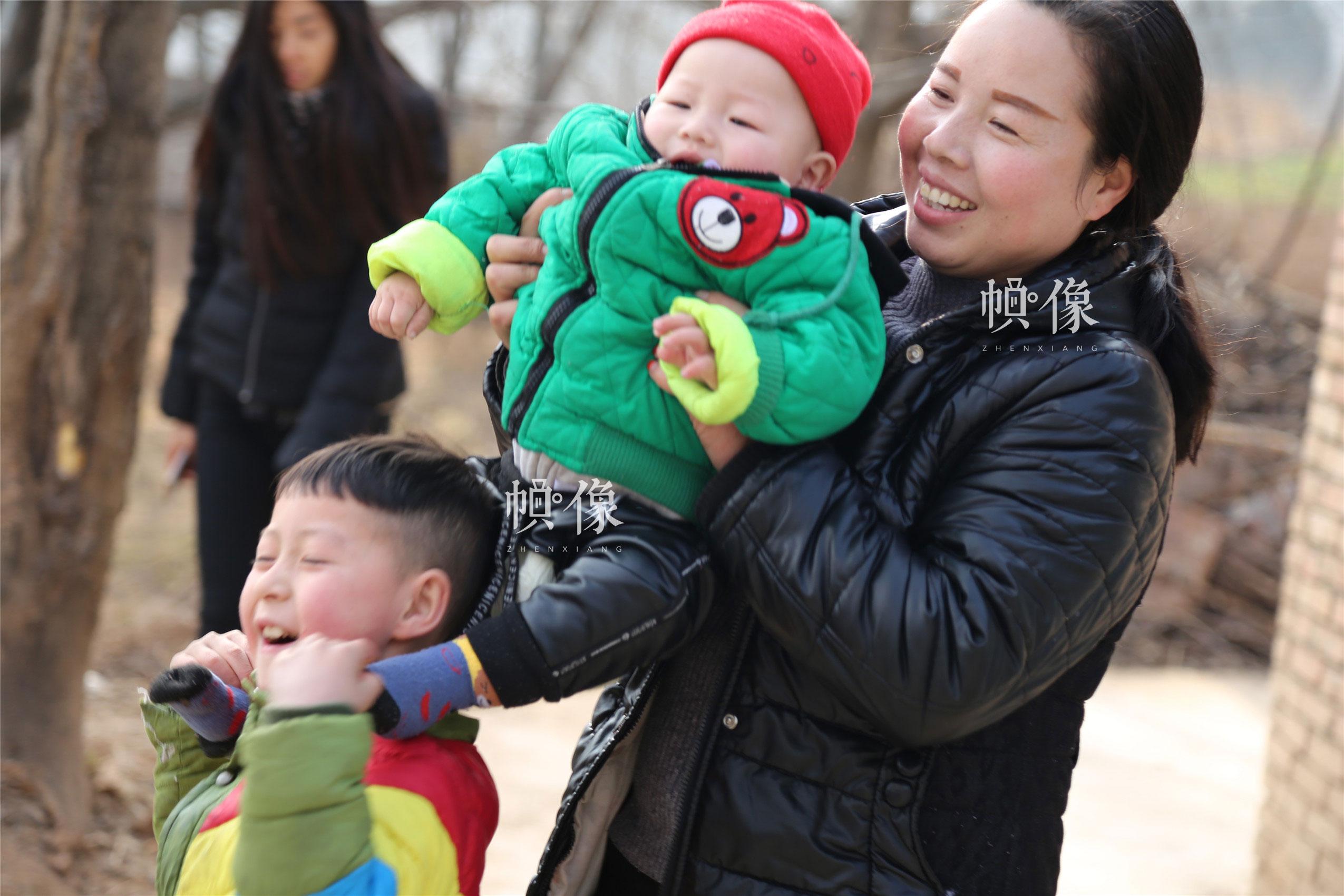 2018年1月22日,甘肃省陇南市西和县,听障儿童潘小明与哥哥和妈妈玩耍。中国网实习记者 李逸奇 摄