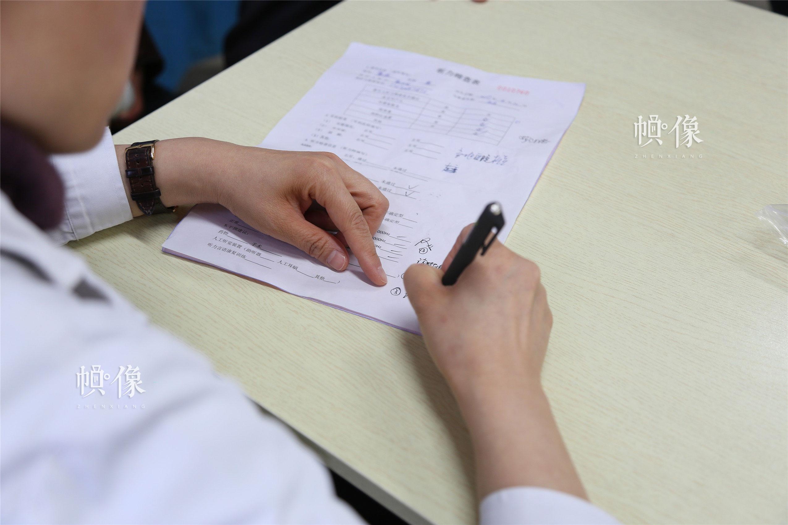 2018年1月21日,甘肃省陇南市西和县,首都医科大学附属北京儿童医院耳鼻咽喉头颈外科科主任、主任医师张杰为听障儿童写诊断。中国网实习记者 朱珊杉 摄