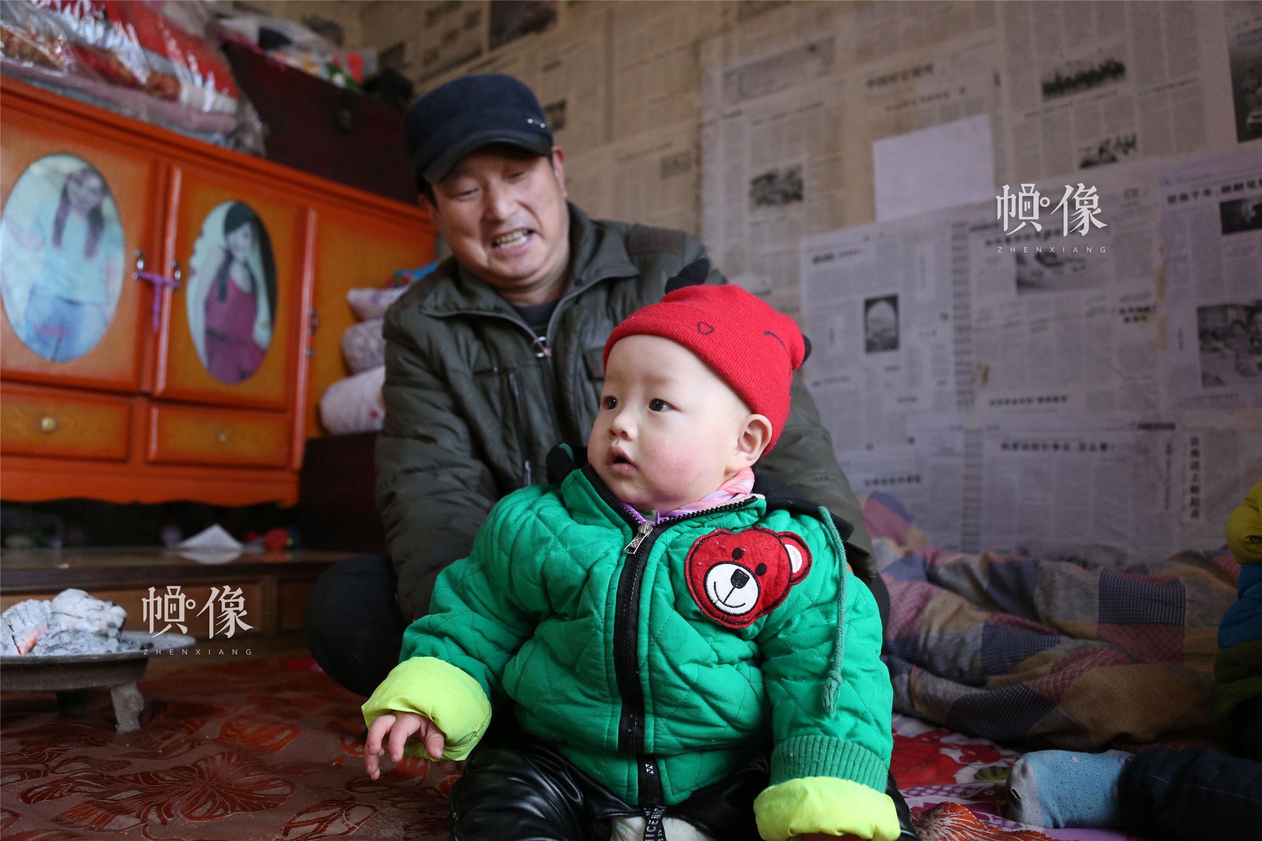 2018年1月22日,甘肃省陇南市西和县,听障儿童潘小明与爷爷玩耍。中国网实习记者 李逸奇 摄
