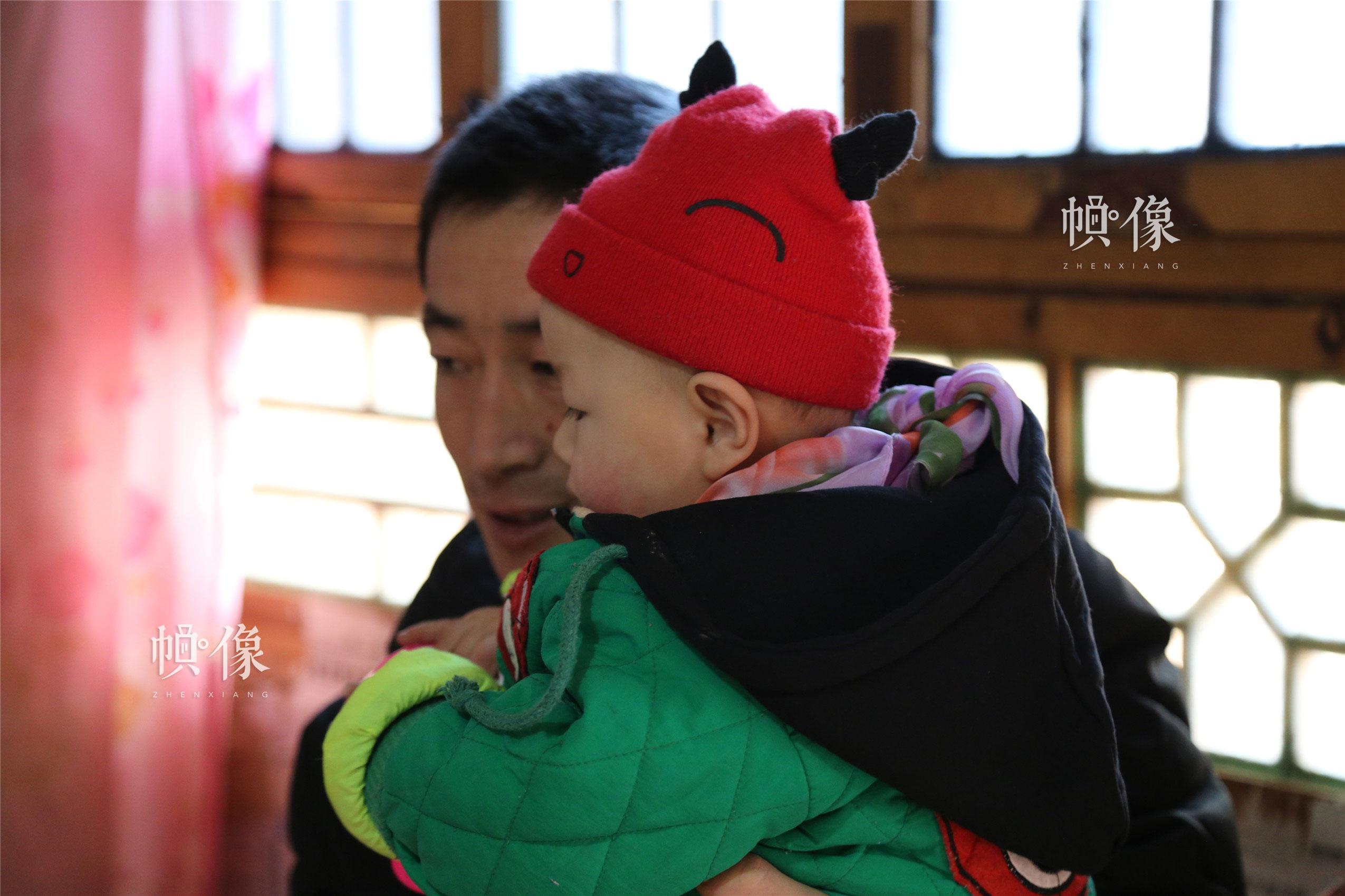 2018年1月22日,甘肃省陇南市西和县,听障儿童潘小明与父亲玩耍。中国网实习记者 朱珊杉 摄