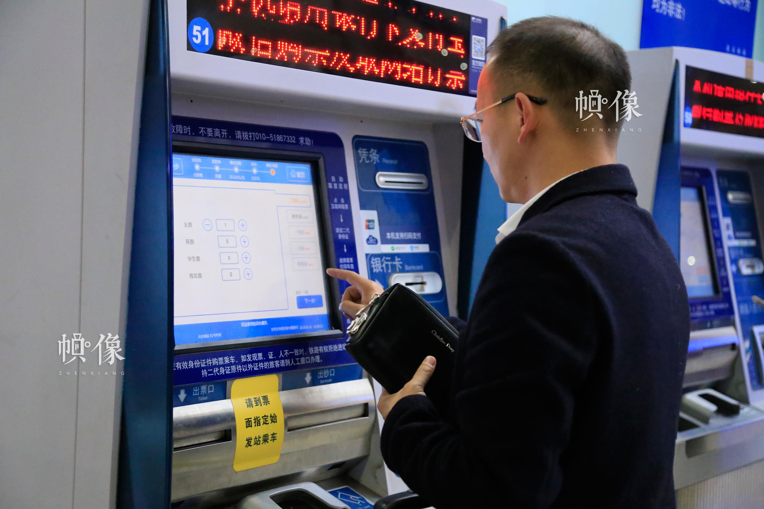 北京南站自助售取票机前,一位乘客购买车票。中国网实习记者 韩依 摄
