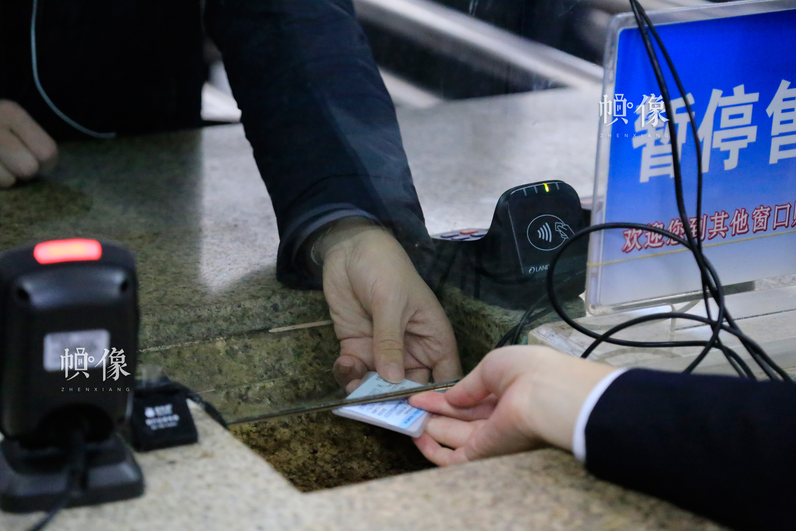 北京南站某一售票窗口内,一位售票员与乘客通过窗口底部的凹槽传递乘客购买的火车票及证件。中国网实习记者 韩依 摄