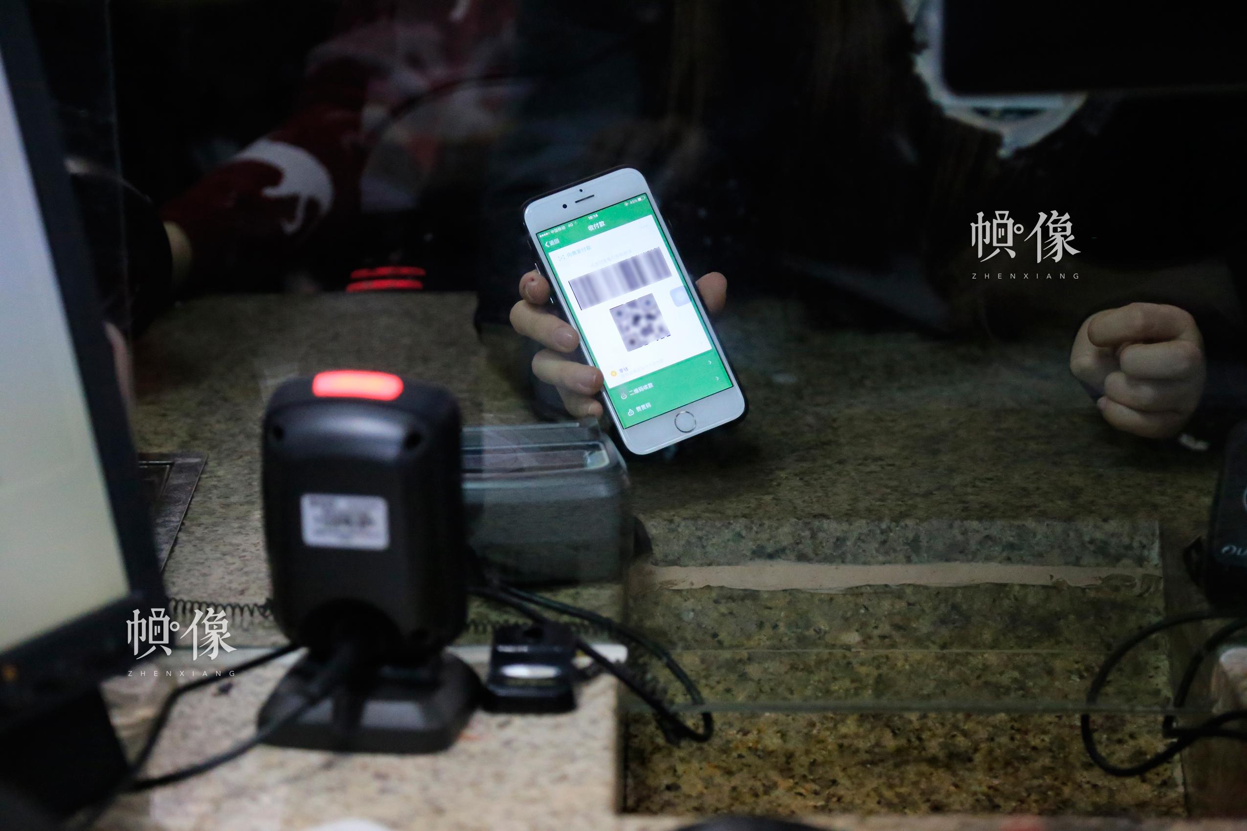 北京南站某一售票窗口处,一位乘客使用微信二维码购票。中国网实习记者 韩依 摄