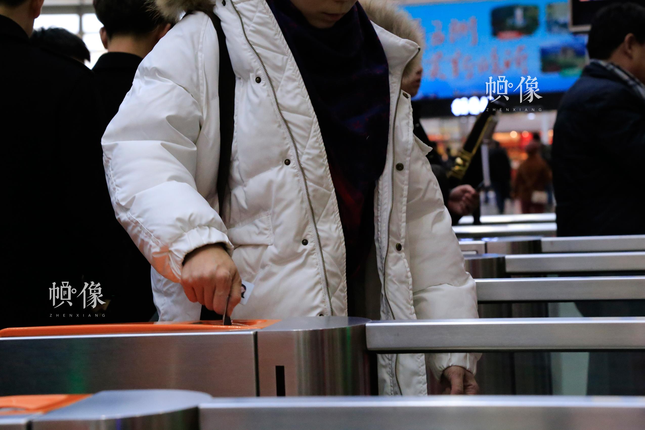 北京南站某检票口前,一位乘客经过闸机自动检票后取回车票。中国网实习记者 韩依 摄