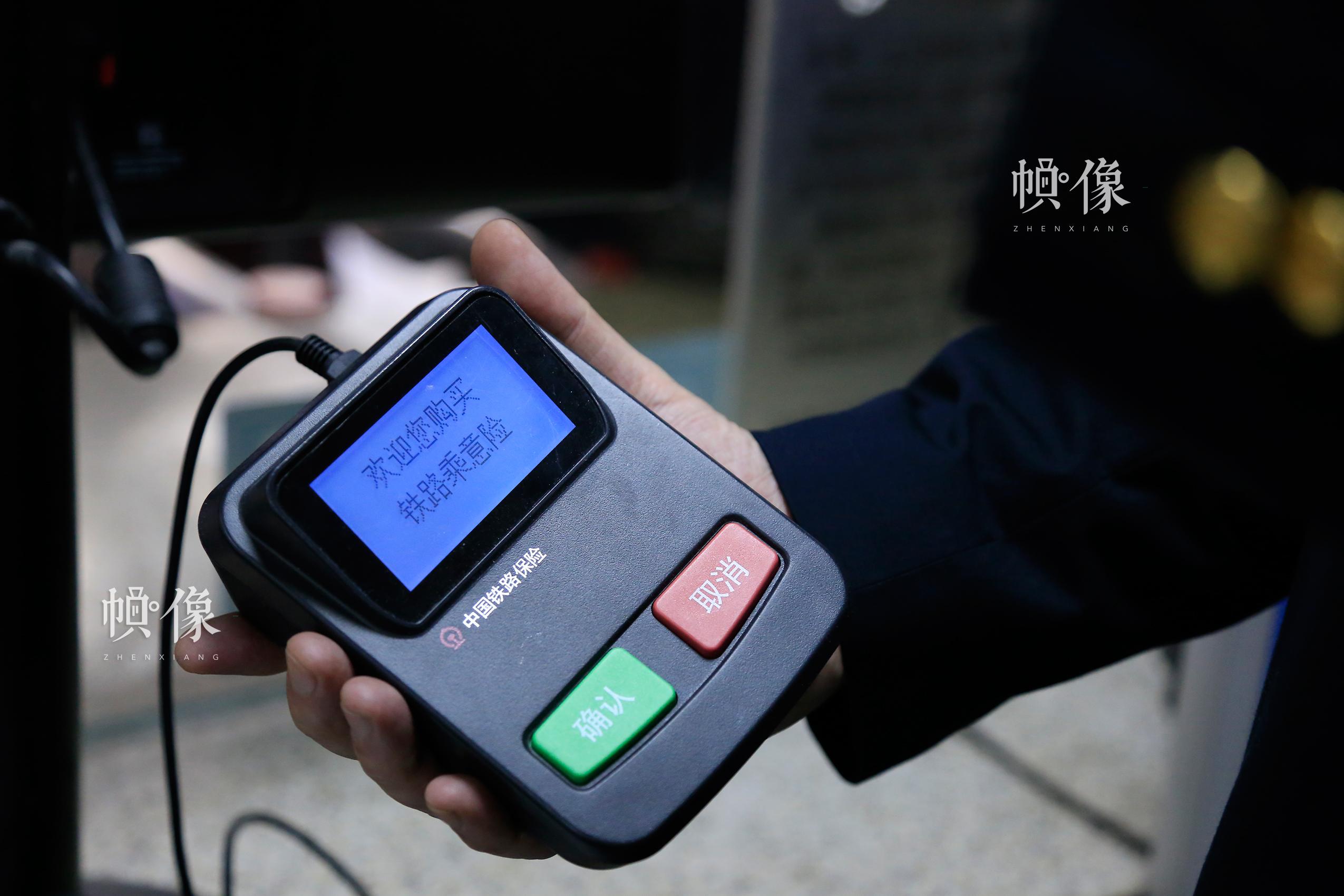 北京南站的某售票车间,工作人员向记者展示铁路乘意险购买器,为旅客出行提供安全保障。中国网实习记者 韩依 摄