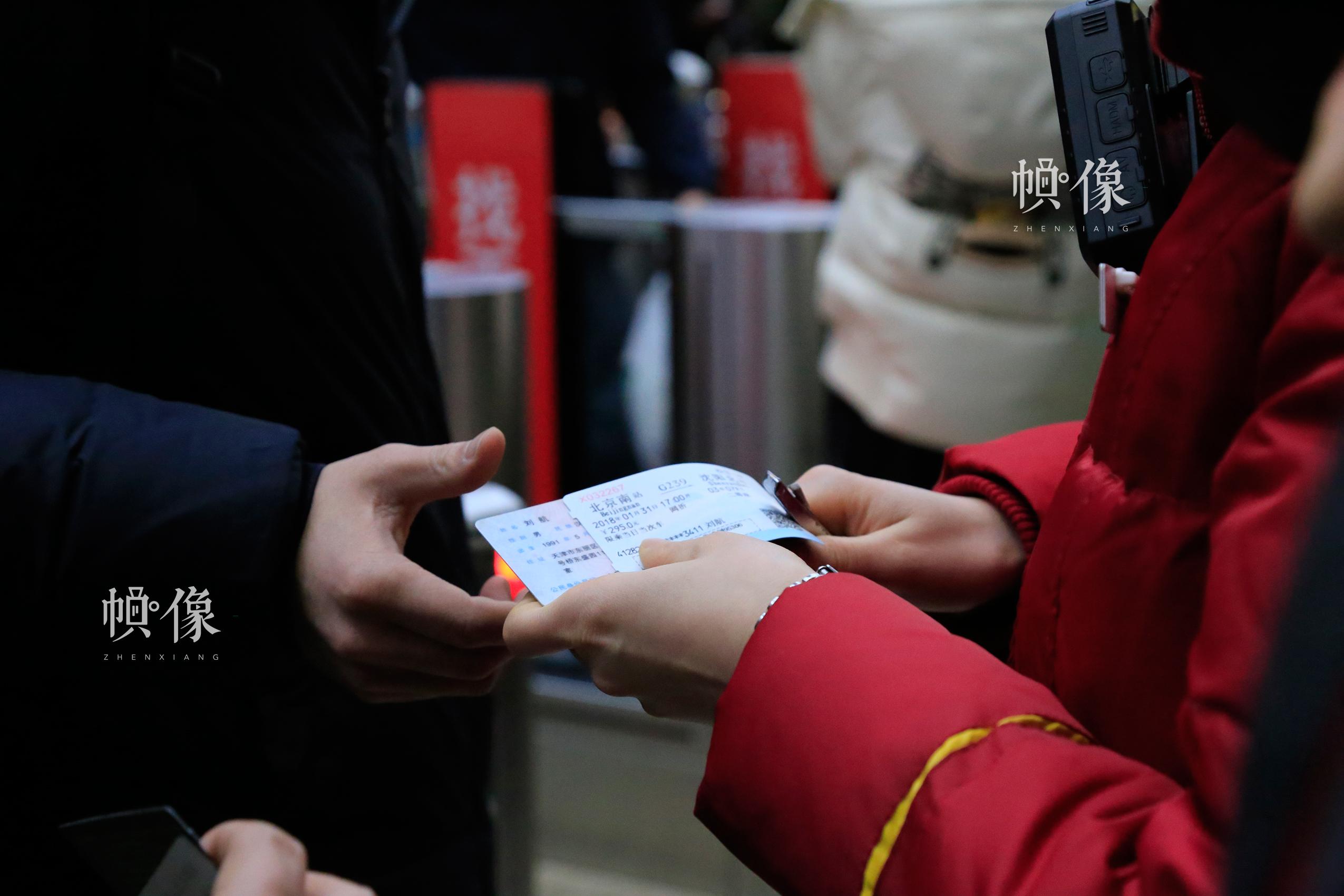 北京南站某检票口前,工作人员手动检票。中国网实习记者 韩依 摄