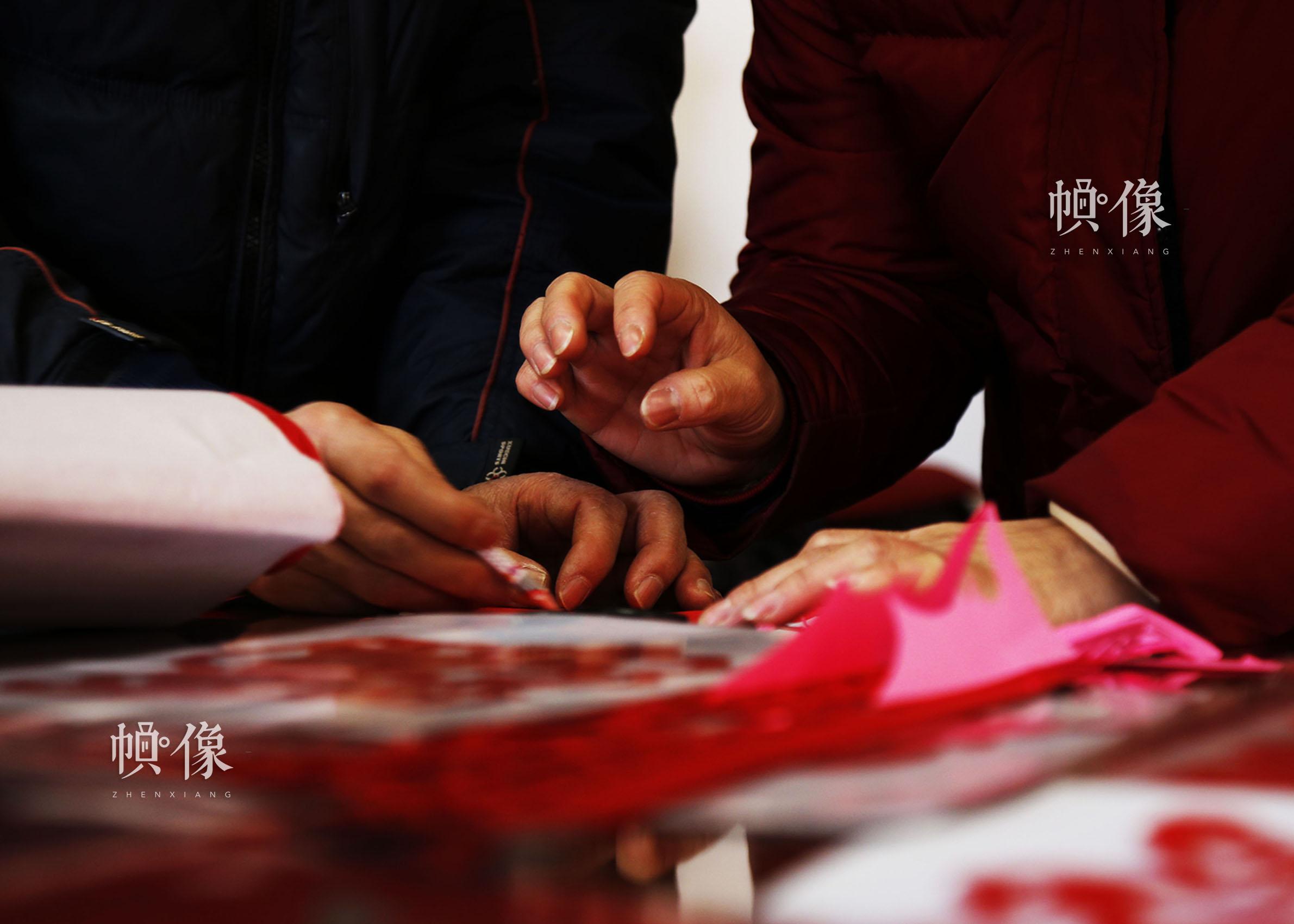 姚雨林指导学生在纸上画剪纸图样。中国网实习记者 张钰 摄