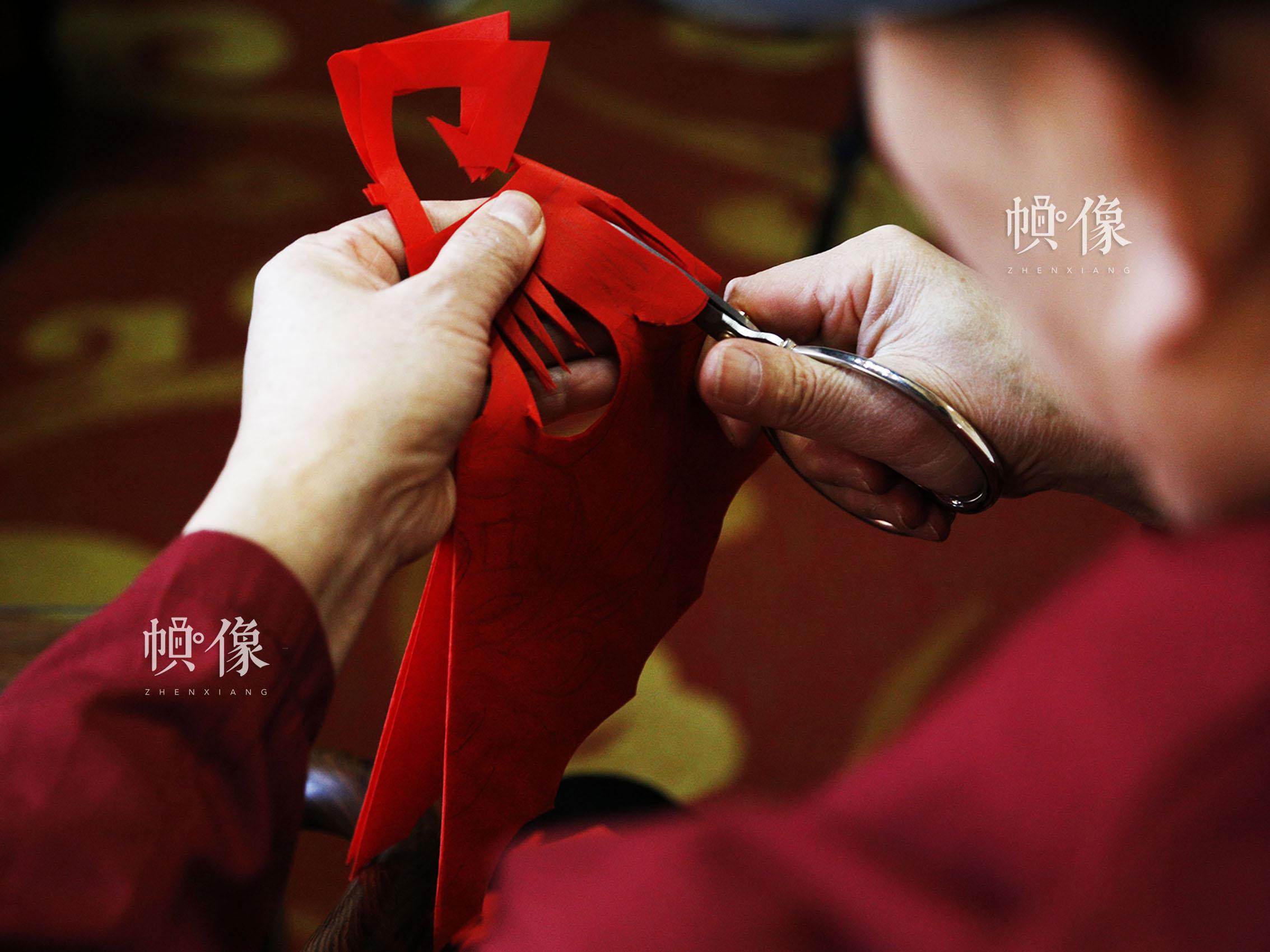 刚刚画好图样的红纸,在姚雨林的手中即将成为一幅窗花作品。中国网实习记者 张钰 摄