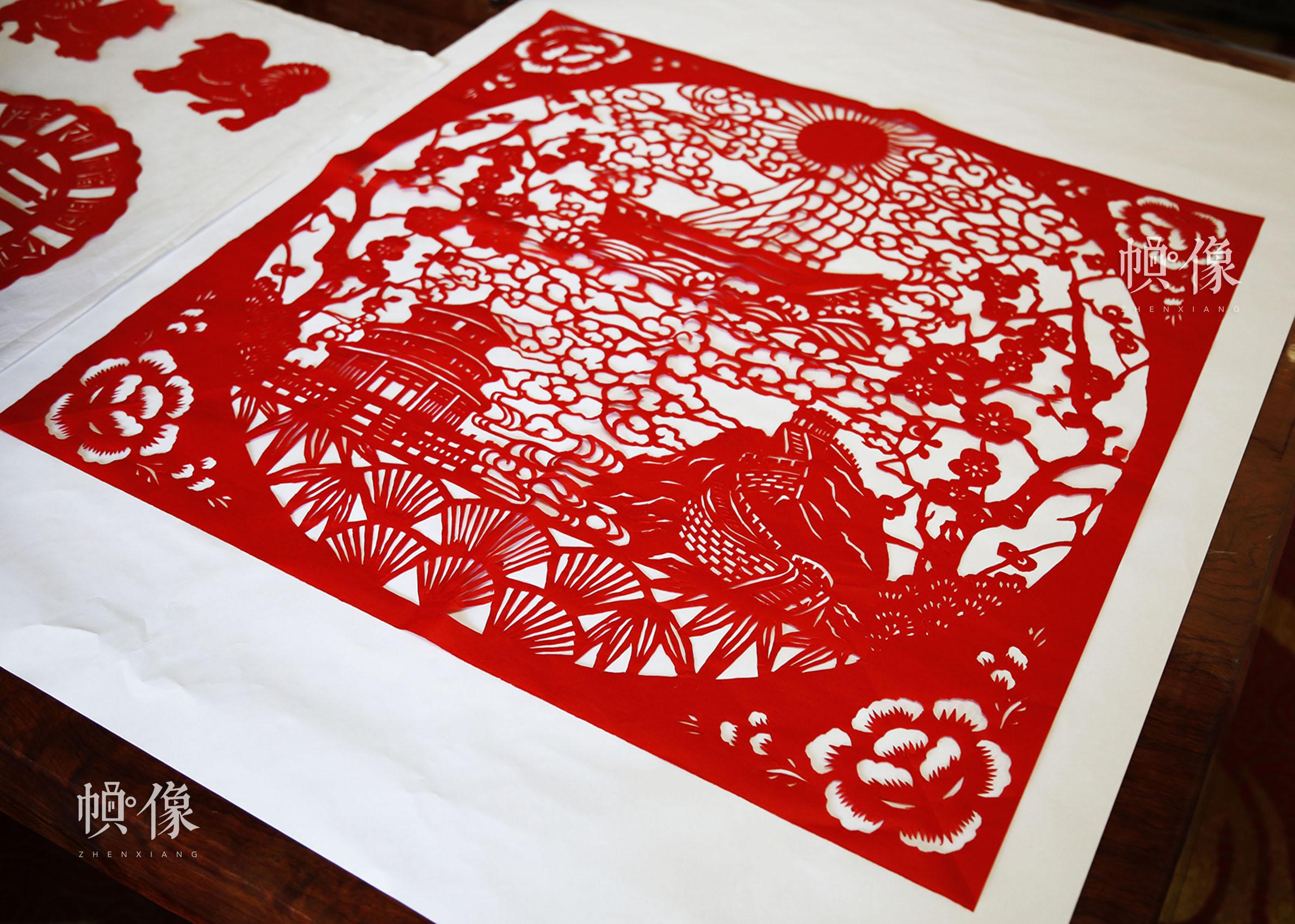 """姚雨林最新制作的剪纸作品,其中包含了""""长城""""""""旭日""""""""帆船""""""""祥云""""等元素,表现了其""""红梅向阳,扬帆远航""""的主题。中国网实习记者 张钰 摄"""
