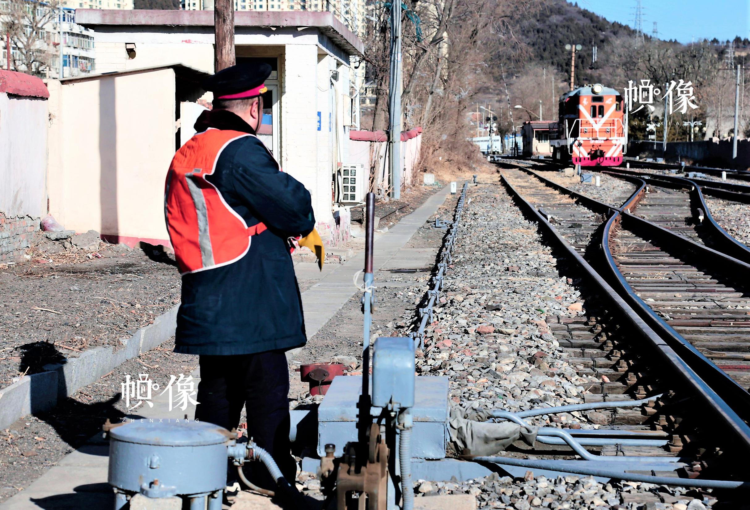 图为铁路扳道员刚刚完成一次铁路扳道工作,等待列车进站。中国网记者 仝选 摄