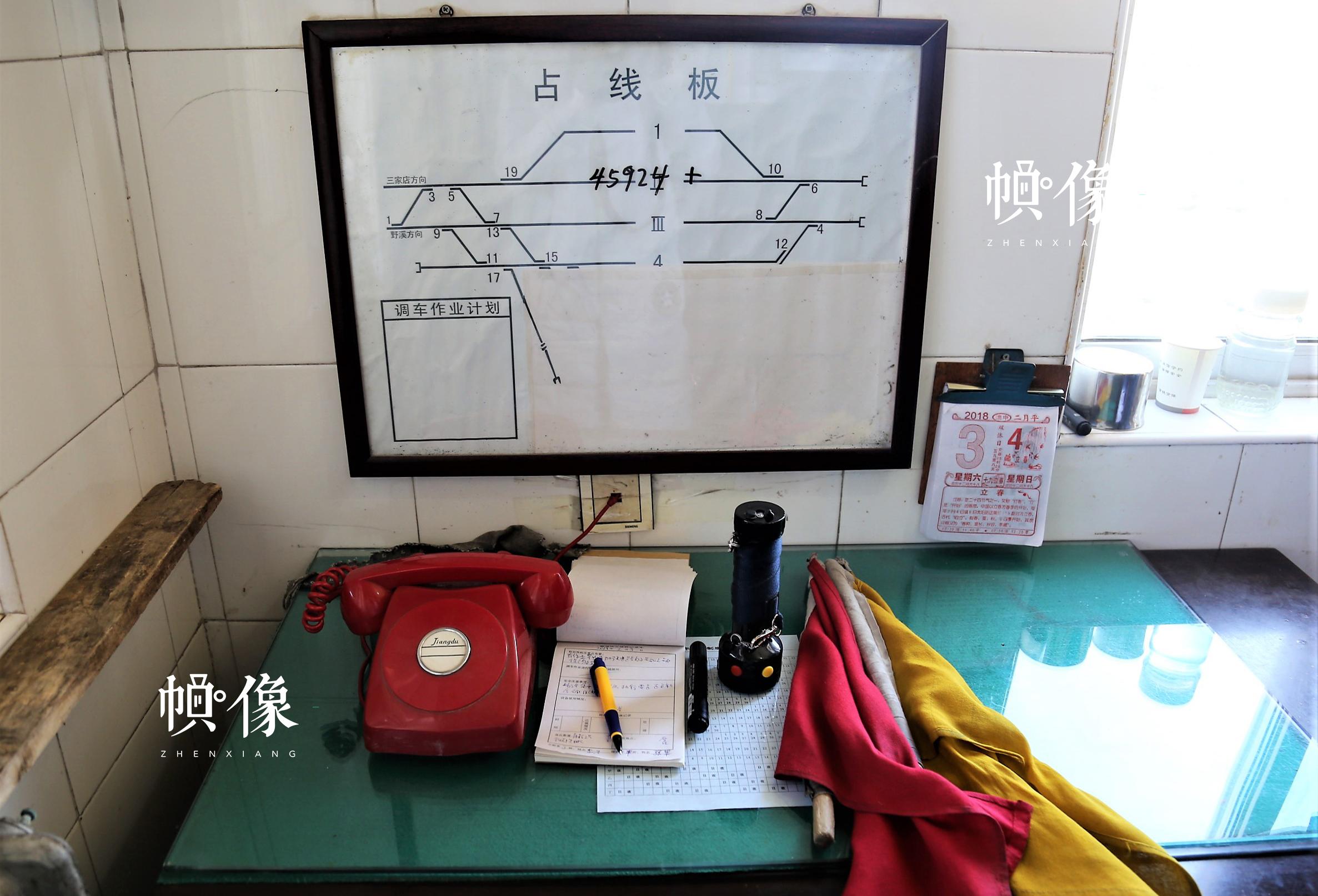 图为铁路扳道员办公桌物品陈列,分别为:指令接收电话、交接班簿、手信号灯、手信号旗。中国网记者 仝选 摄