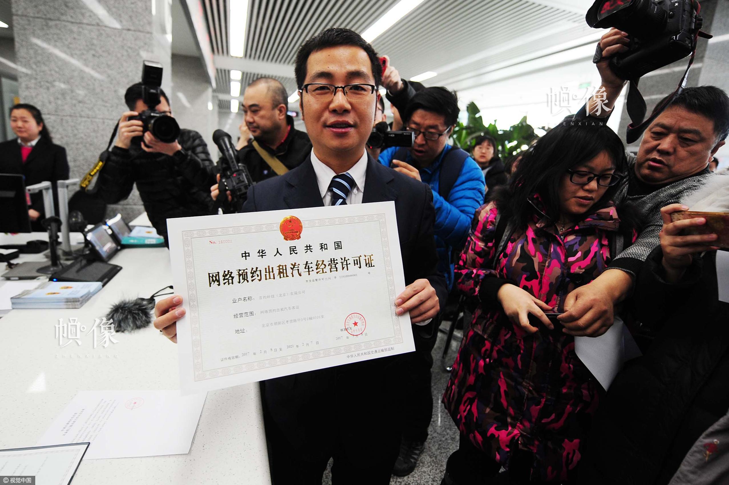 2017年2月8日,北京,首汽约车负责人第一时间来到北京市政务服务中心,工作人员向首汽约车颁发北京网约车平台经营许可证。这是北京发放的首家省一级平台资格许可证。图片作者:北京青年报 袁艺/视觉中国