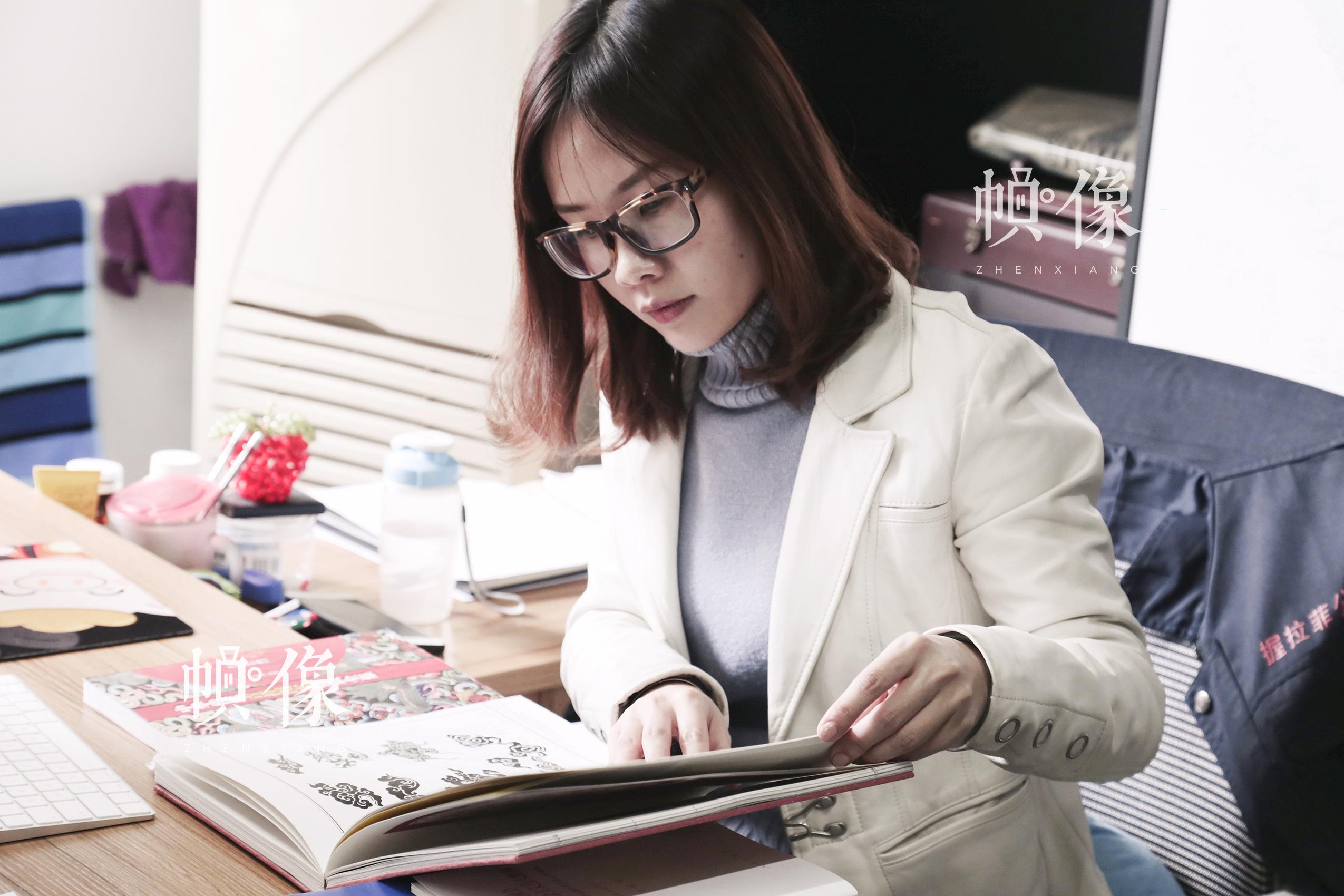 2018年3月3日,全国人大代表、北京工美集团握拉菲首饰有限公司设计部主任侯湛莹翻看设计书籍寻找设计灵感。中国网实习记者 张颖颖 摄