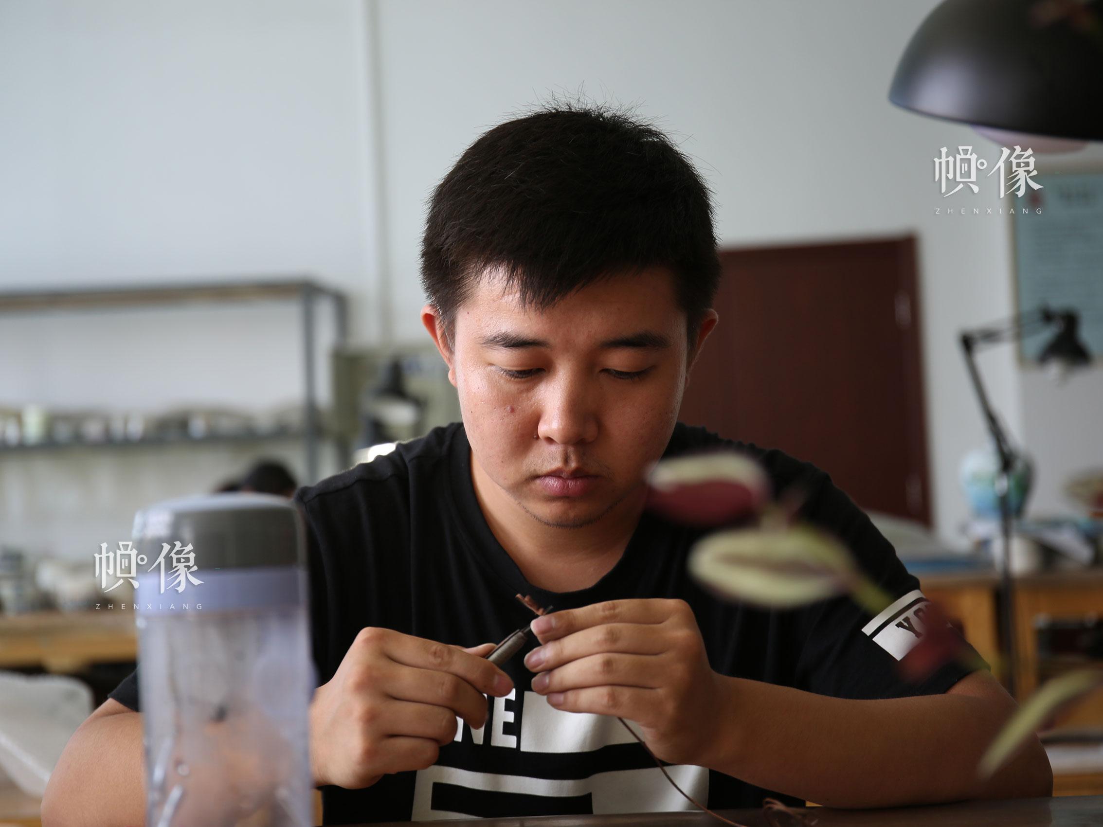 """2017年9月5日,北京工美集团景泰蓝工匠进行""""掐丝""""工艺。中国网记者 赵超 摄"""