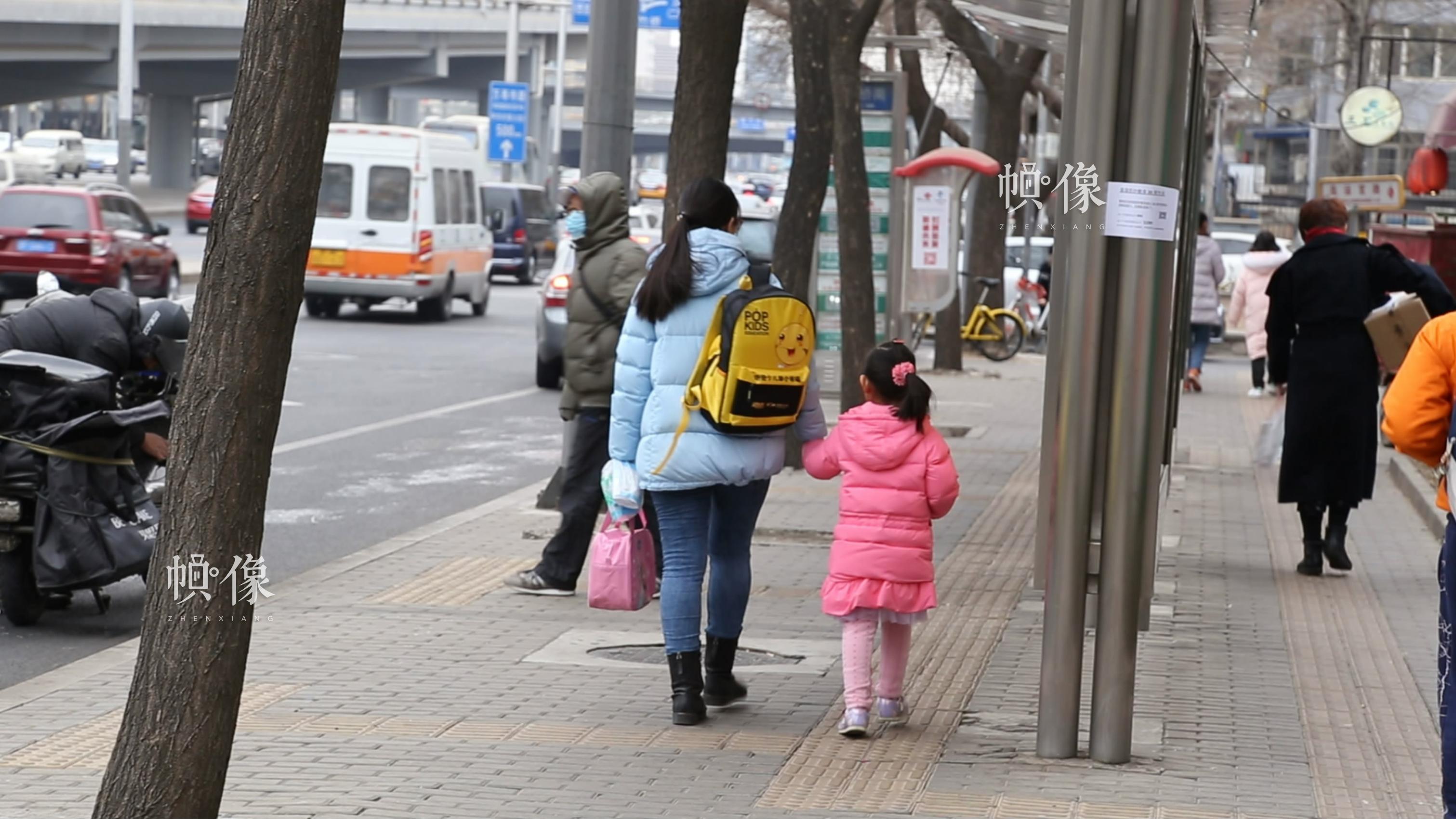 2018年3月6日下午,北京海淀實驗小學附近,一女子牽著剛下學的女兒走在回家的路上。中國網記者 趙超 攝