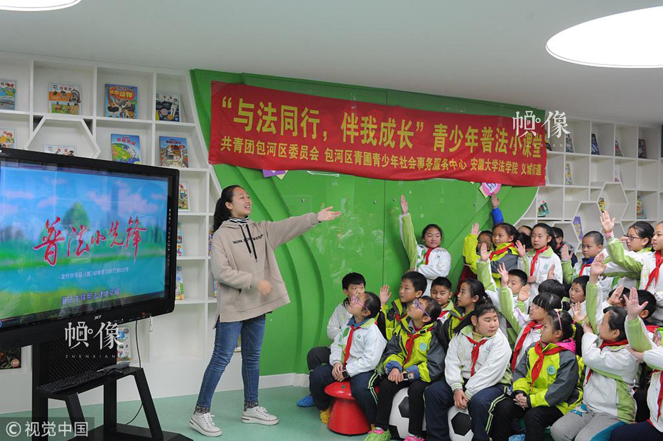 """2017年11月30日,合肥,法学院志愿者在普法小课堂与学生互动。当日,中国法制宣传日即将来临之际,在安徽合肥义城街道华山路小学,开展""""与法同行,伴我成长""""青少年普法小课堂活动。通过现场教学,互动交流,观看视频的方式,将未成年人保护法、交通法带入学校,普及给同学们,营造良好的知法懂法守法的氛围。视觉中国"""