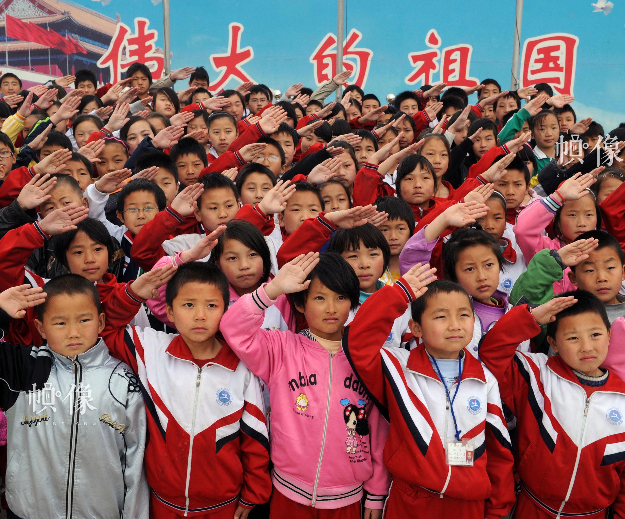 2009年4月,山东日照安康家园,参加升旗仪式的孩子们行少先队礼。雷声 摄