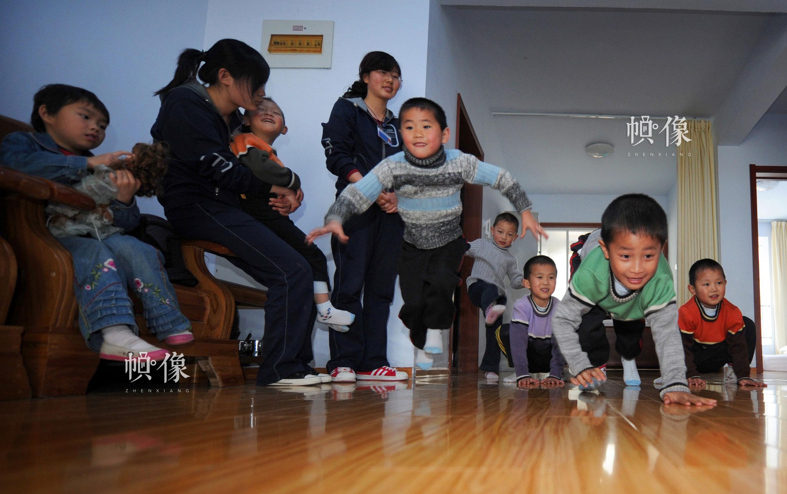 """2009年4月,山东日照安康家园,""""安康妈妈""""李向南(站立者)带着孩子们一起做游戏。雷声 摄"""
