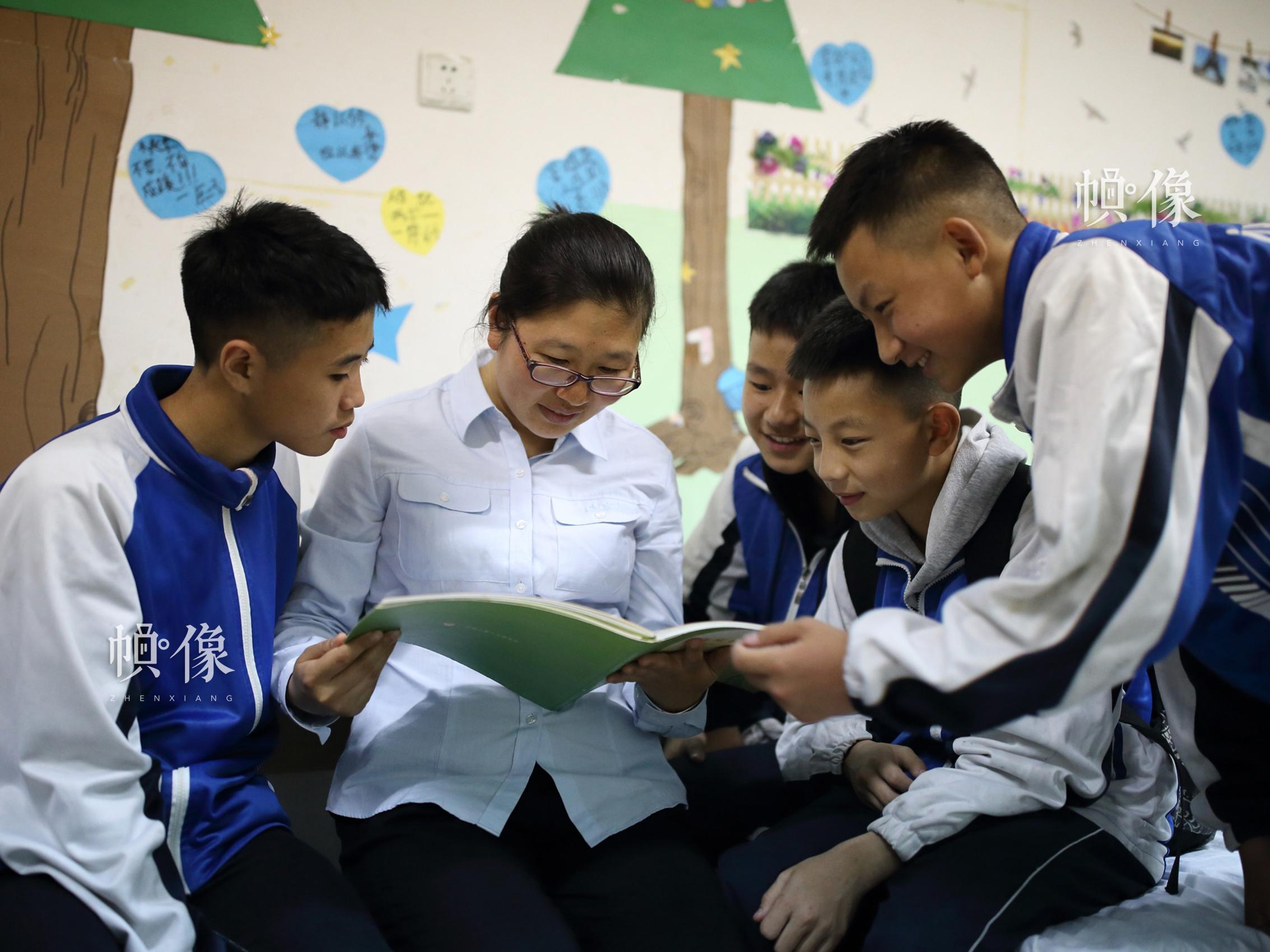 """2018年4月,孩子们和前来成都双流安康家园看望他们的日照""""安康妈妈""""李向南一起看照片。中国网记者 陈维松 摄"""