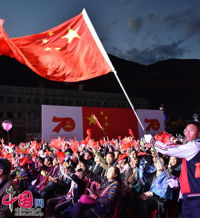 小萝莉的落照_晚会现场气氛热烈,当地百姓手挥小红旗,沉浸在晚会的欢乐气氛中.