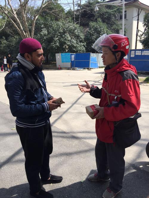 Китайский доставщик свободно общается с иностранным заказчиком студентом по-английски