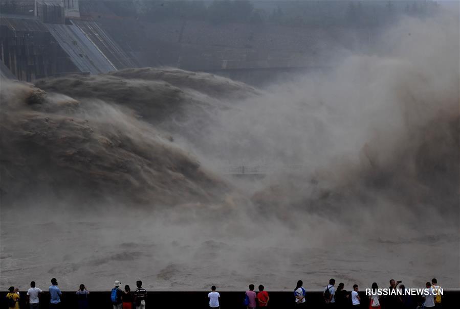 """На гидроузле """"Сяоланди"""", построенном на реке Хуанхэ в провинции Хэнань /Центральный Китай/, начали противопаводковый сброс воды. Многочисленные туристы собрались посмотреть на бурлящие потоки воды, наполненные песком и илом."""