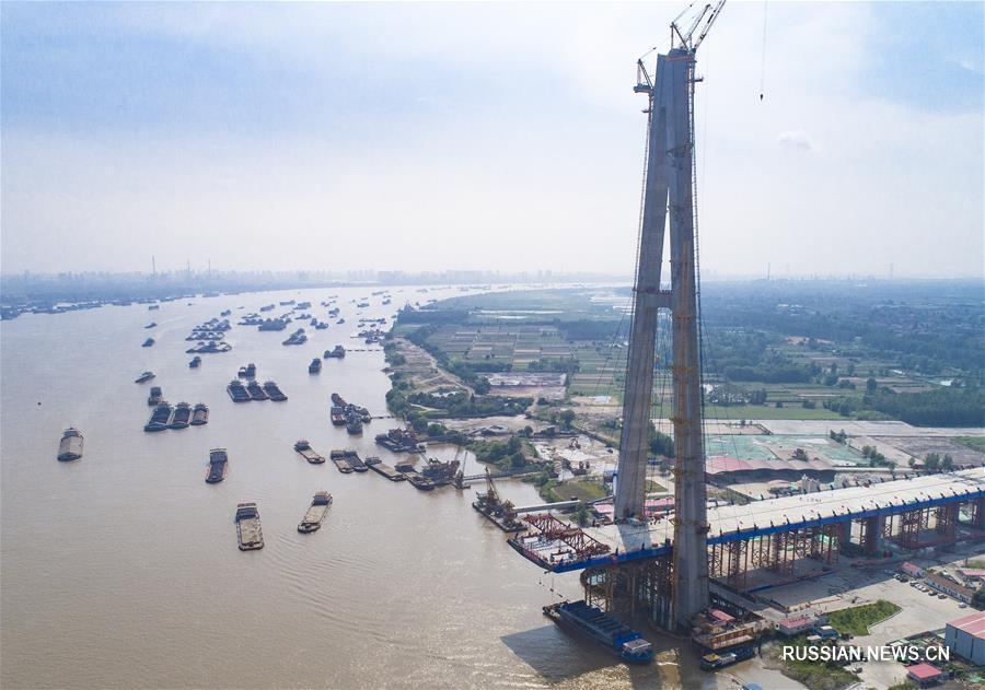 """На строительстве большого моста """"Циншань"""" через реку Янцзы в городе Ухань /провинция Хубэй, Центральный Китай/ сегодня завершился монтаж первой стальной коробчатой балки основного пролета. Это значит, что строительные работы вступили в решающую стадию."""