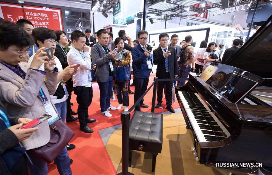 """На фото -- посетители знакомятся с """"умным"""" роялем Steinway, умеющим записывать и точно воспроизводить мелодии, сыгранные исполнителем."""