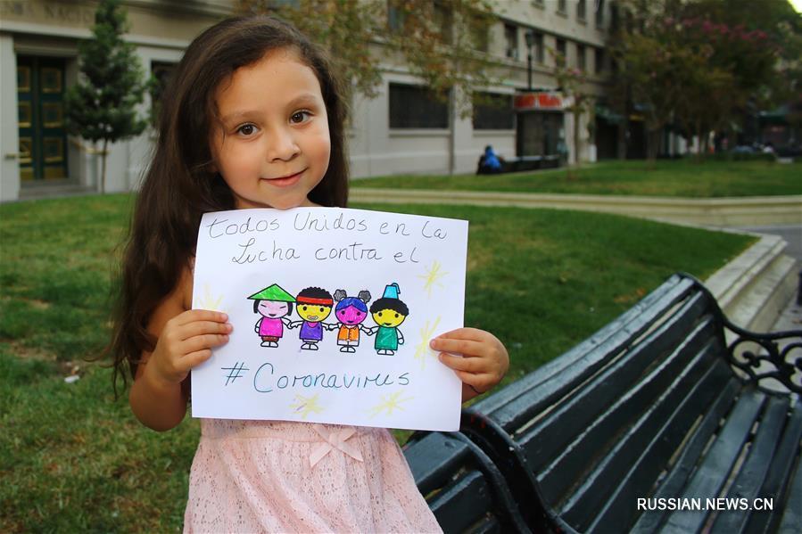"""На фото от 10 февраля -- 5-летняя жительница чилийской столицы Сантьяго Данна Суарес показывает свой рисунок, на котором написано: """"Китай, ты обязательно сможешь! Сплотимся для борьбы с коронавирусом! Чили вместе с тобой!"""""""