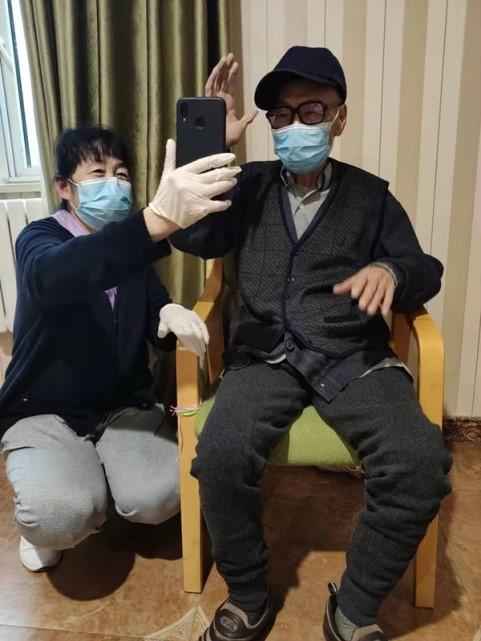 Пожилой постоялец пансионата для престарелых с помощью персонала общается со своими родными по видеозвонку