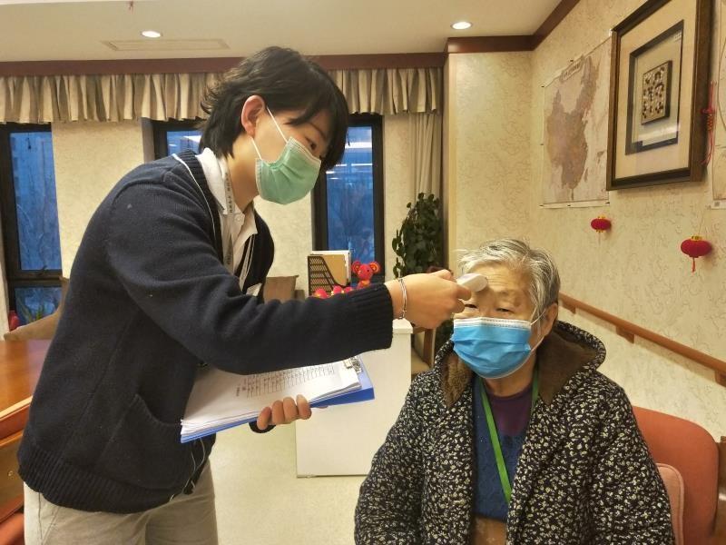 Работница дома престарелых измеряет пожилой женщине температуру