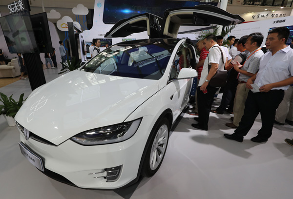 Visitors check out a Tesla intelligent car displayed at the 2017 Seventh China Smart City Technology and Application Products Expo in Ningbo, Zhejiang province, on Sept 8. [Photo provided to China Daily]