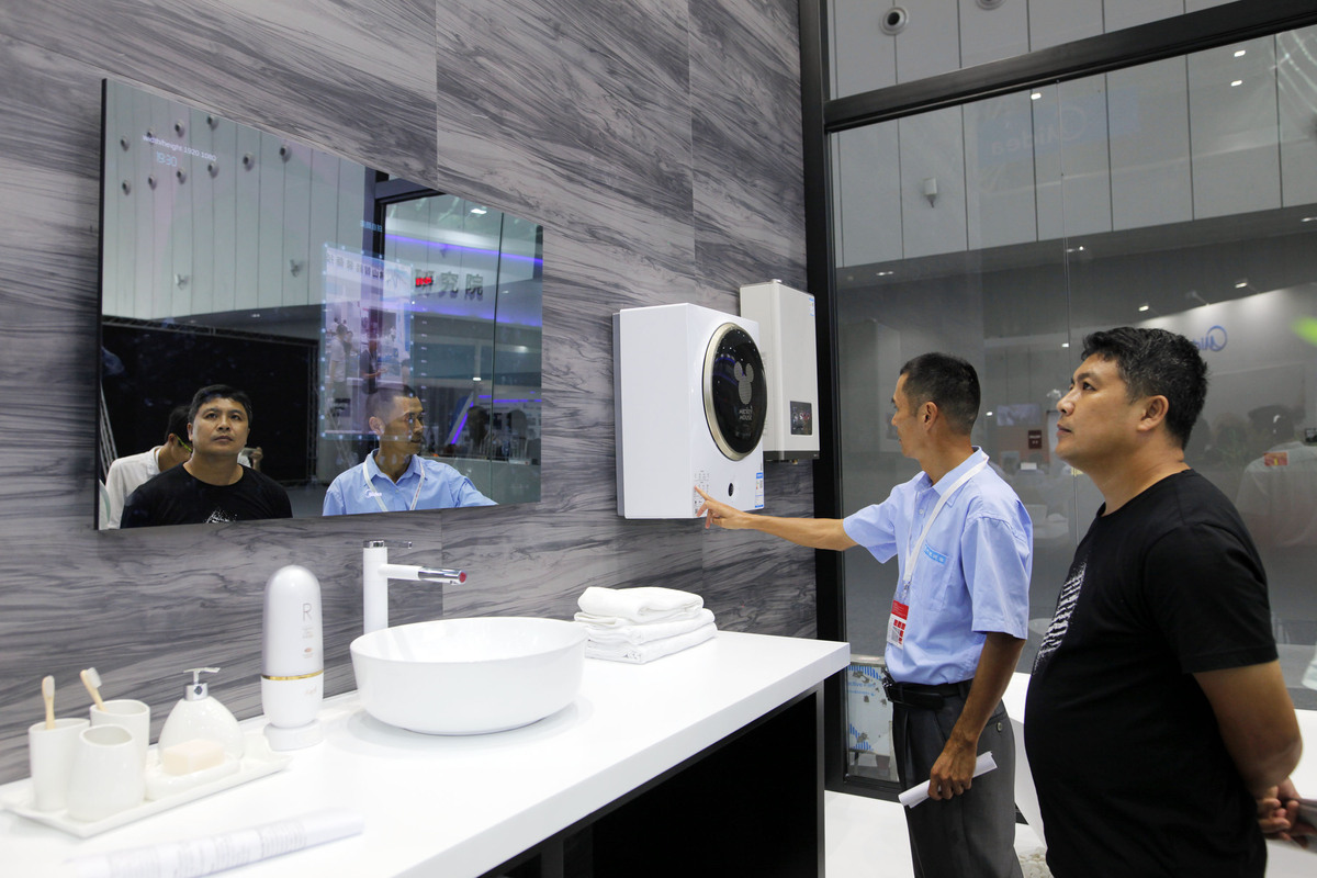 "Visitors look at a ""smart mirror"", which can monitor people's skin conditions, at the smart home products center of leading Chinese home appliance maker Midea Group in Foshan, South China's Guangdong province. [Photo/China Daily]"