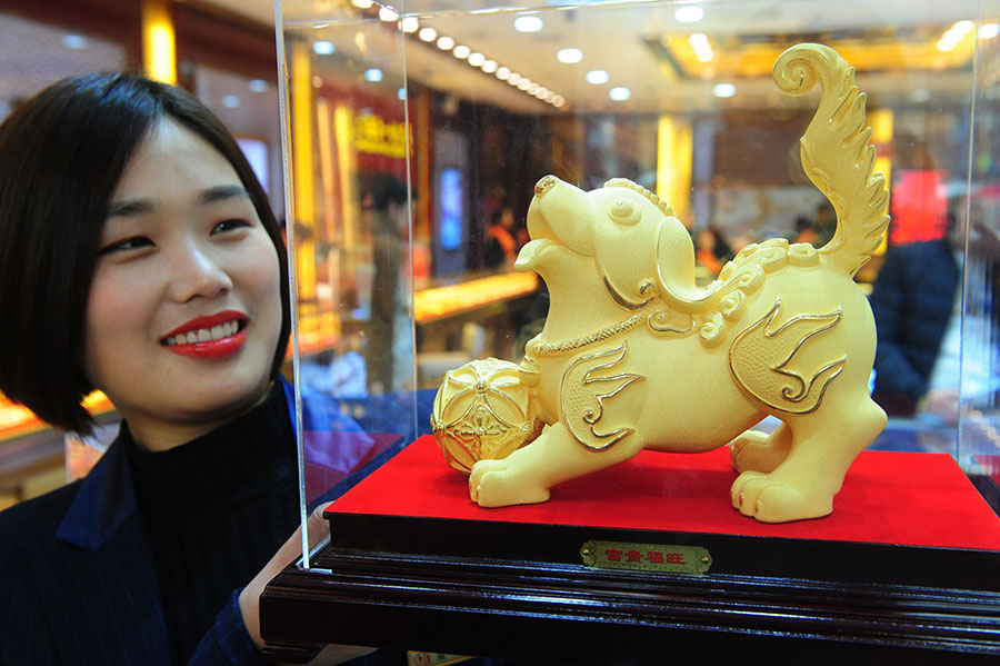 An employee of a jewelry shop in Fuyang, Anhui province, displays a dog statue made of gold. [Photo/China Daily]