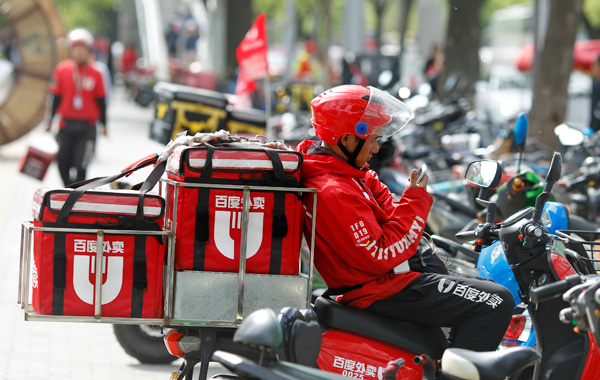 A Baidu Waimai delivery worker receives online food orders on his phone in a street in Beijing. [Photo/China Daily]