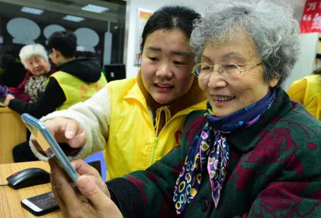 An 80-year-old woman named Ge Yuqi is learning how to use social application WeChat with the help of a volunteer on January 16, 2018. [Photo/People's Daily Online]