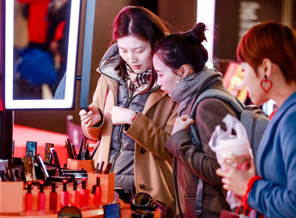 Consumers choose cosmetics at a department store in Shanghai. [Photo provided to China Daily]