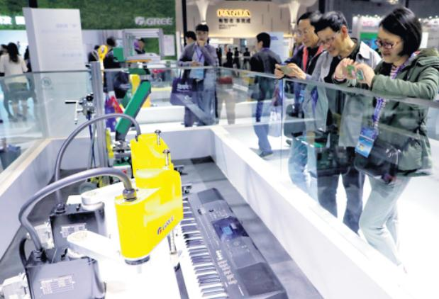 A robot made by Gree plays piano at the China International Industry Fair in Shanghai on Nov 8. [Photo/China Daily]