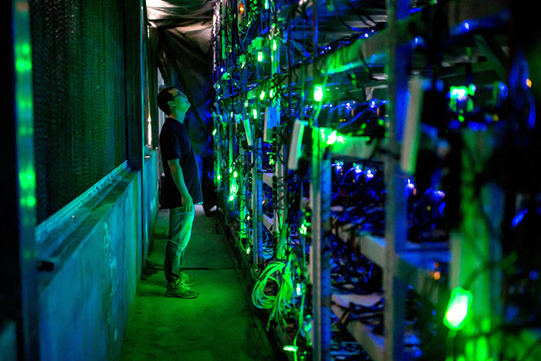 A technician checks mining equipment at a bitcoin mine in Sichuan province. [Photo/China Daily]