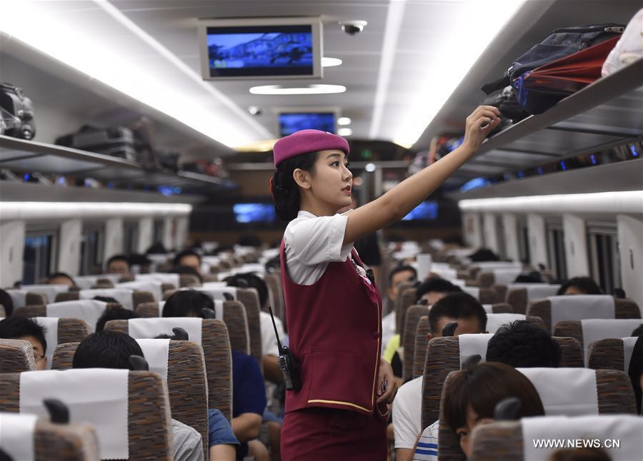 A conductor arranges suitcases in the Fuxing train on the Beijing-Tianjin Intercity Railway Aug. 21, 2017. [Photo/Xinhua]