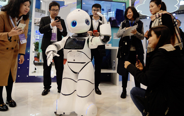 Visitors interact with a robot during an AI expo in Nanjing, East China's Jiangsu Province. [Photo/China Daily]
