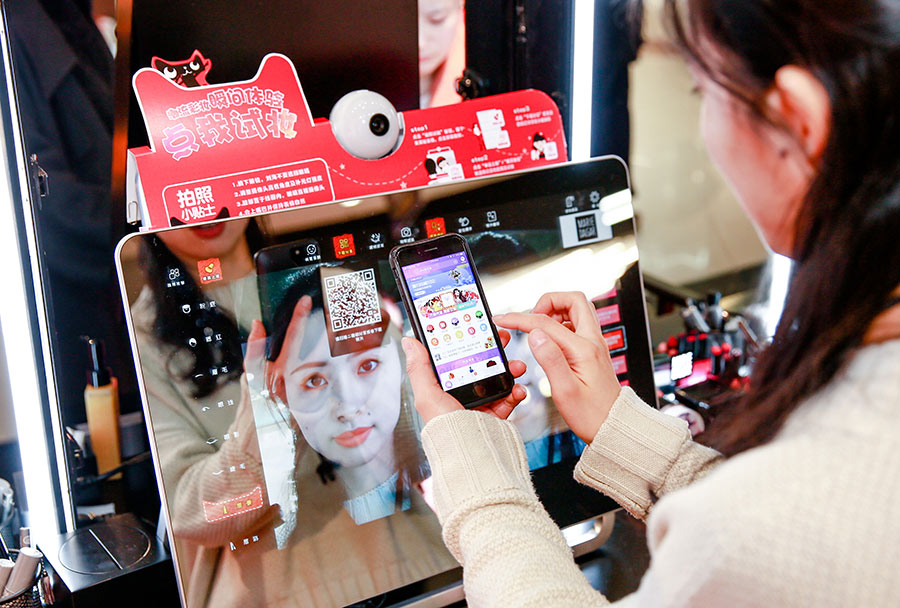 A customer uses a mobile app to select cosmetics for trial at a Tmall pop-up store in a shopping mall in Shanghai. [Photo provided to China Daily]