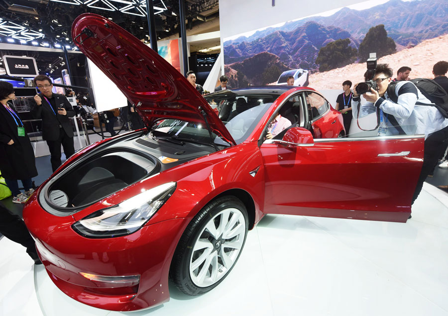 Visitors take photographs of a Tesla electric car at an automobile exhibition held in Beijing. [Photo/China Daily]