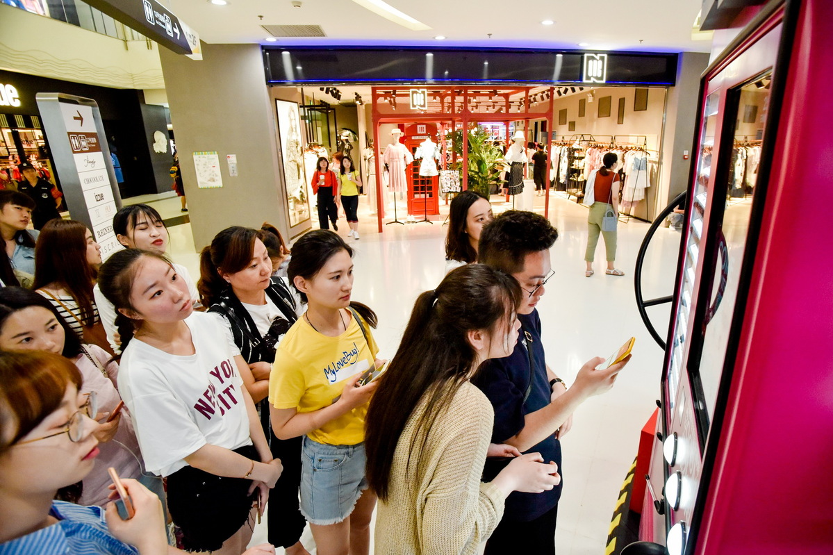 Customers queue to pay through QR code scanning at a Tmall pop-up store in Beijing.[Photo/China Daily]