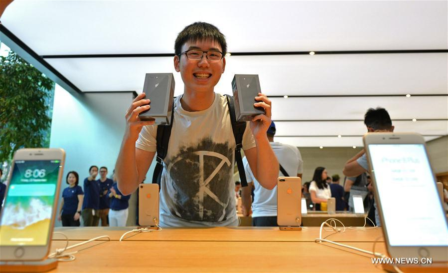 A customer poses with his iPhone 8 and iPhone 8 plus at an Apple Store in Singapore, on Sept. 22, 2017. [Photo/Xinhua]
