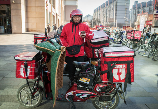 A Baidu Waimai courier checks his cellphone while taking a break alongside his vehicle in Beijing. [Photo/Xinhua]