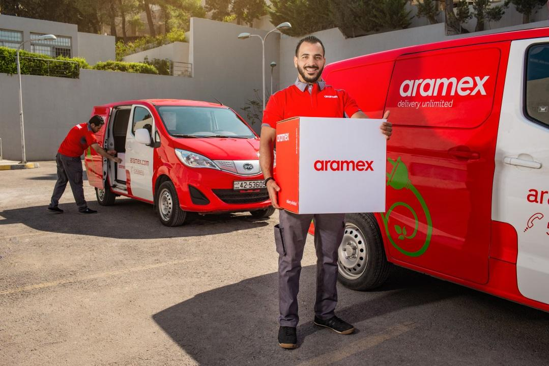 An Aramex employee stands proudly next to a BYD T3. The company ordered 10 BYD T3s after a successful five-month trial in 2017. [Photo courtesy of BYD]
